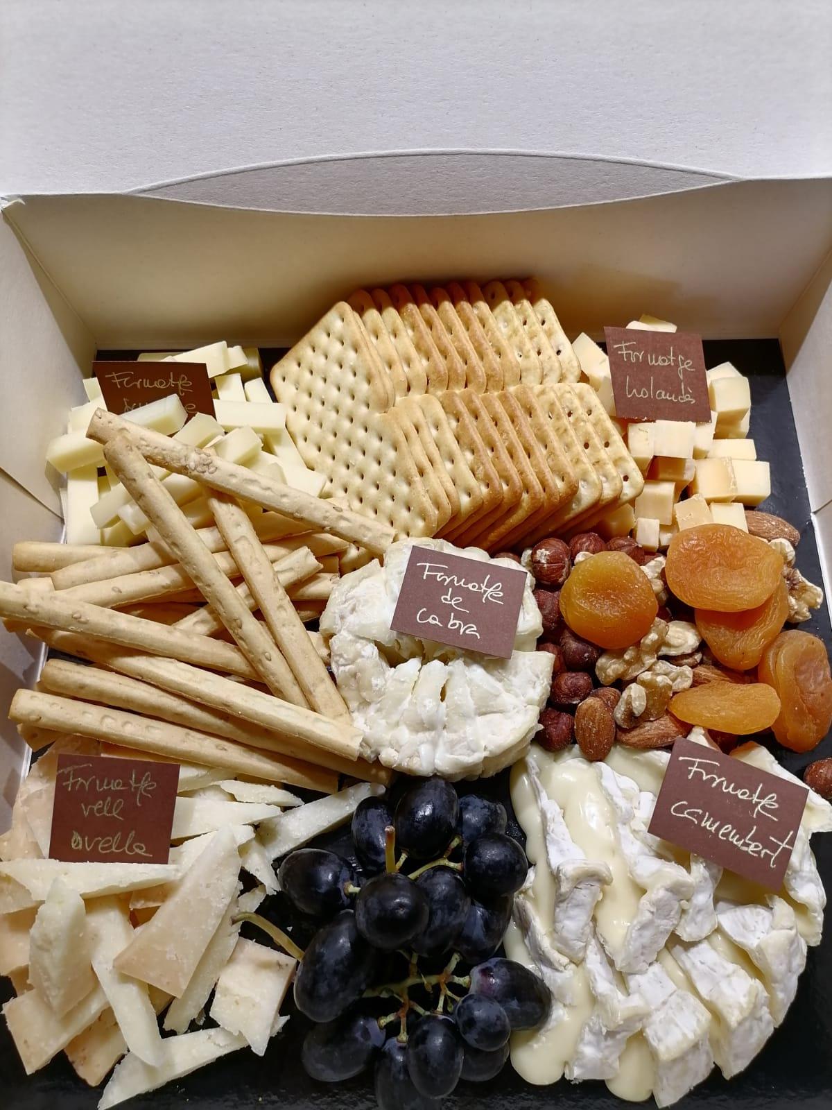 Taula de formatges de 5 tipus amb bastonets, crackers de pa, raïm i fruits secs